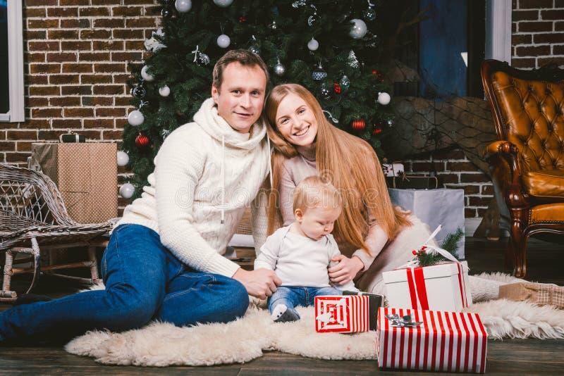 Noite comemorativo do Natal da família Povos caucasianos da família três que sentam-se sob a árvore de Natal da árvore conífera n imagens de stock royalty free