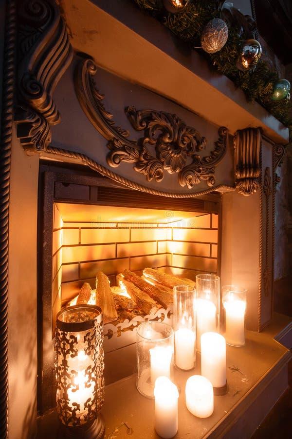 Noite de Natal chaminé na sala com velas o abeto vermelho decorou balões imagens de stock