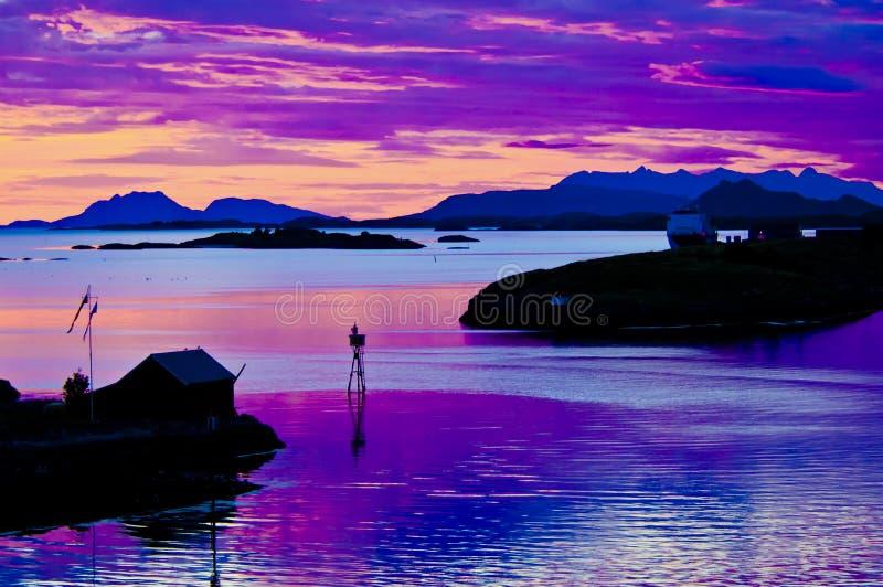 Noite de plenos verões em Noruega, céu colorido, refletindo no mar