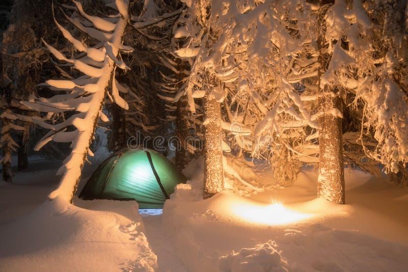 Noite disparada de fogo ardente, exposição longa, dormindo na parte externa da neve A noite acampa nas montanhas Tempo do Natal imagens de stock royalty free