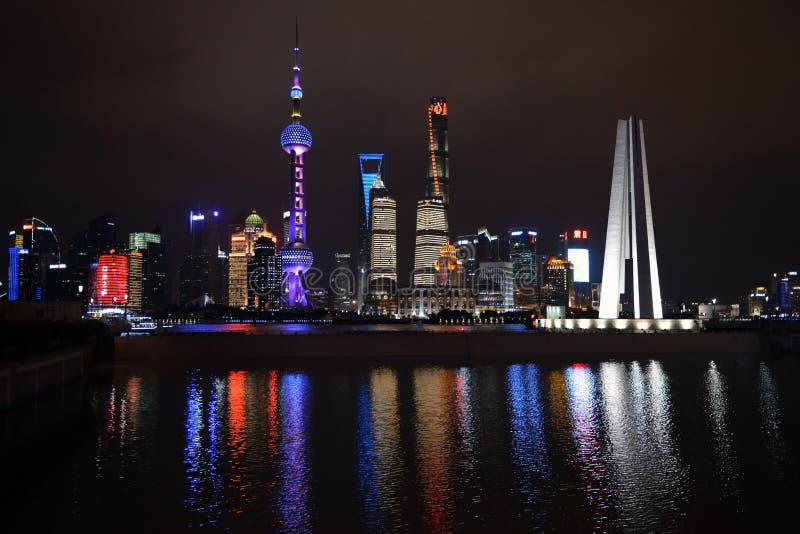 A noite disparou da skyline de Shanghai com o monumento ao ` s dos povos nela imagens de stock