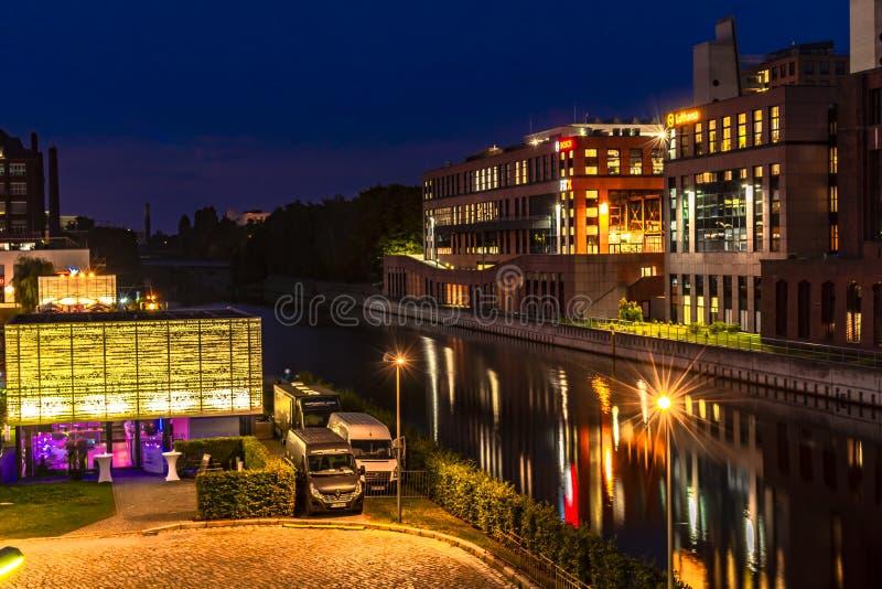 A noite disparou de um porto no canal de Teltow em Berlim-Tempelhof com armazéns velhos Há igualmente restaurantes com luz colori foto de stock