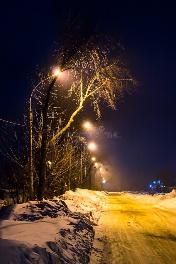 Noite do inverno iluminada pelo villige vazio da rua das lanternas foto de stock royalty free
