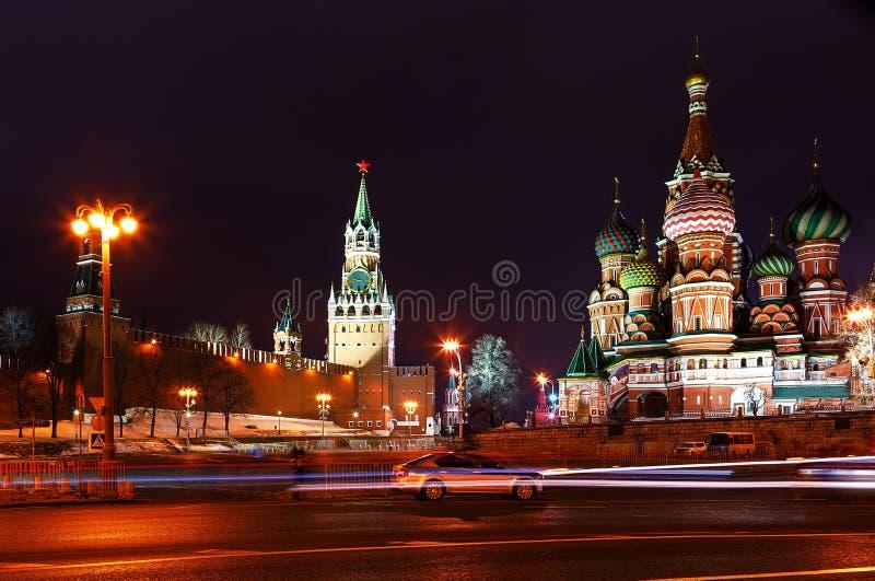 Noite do Kremlin de Moscou A catedral e Spasskaya do ` s da manjericão do St elevam-se no fundo dos traços de faróis do carro fotos de stock royalty free