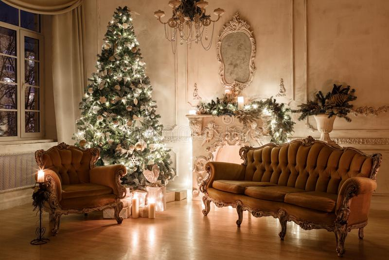 Noite do Natal pela luz de vela apartamentos clássicos com uma chaminé branca, uma árvore decorada, sofá, grandes janelas e fotos de stock