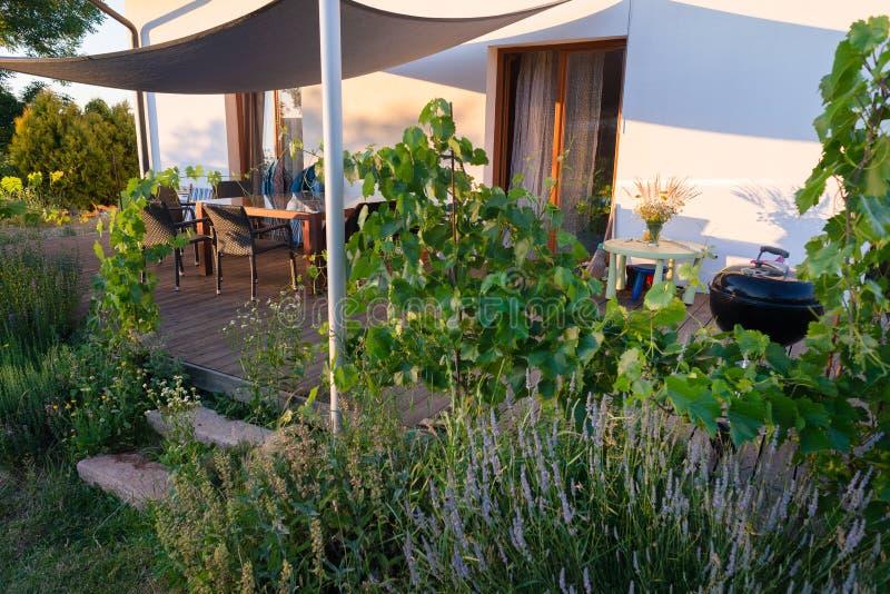 Noite do verão do BBQ da tabela das flores da máscara do pátio do terraço do jardim foto de stock royalty free