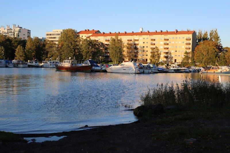 Noite do verão em Helsínquia, Finlandia - luz natural morna, mar, barcos, casas e algumas árvores foto de stock