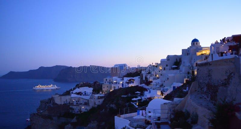 Noite em Oia com luzes e navio de cruzeiros foto de stock