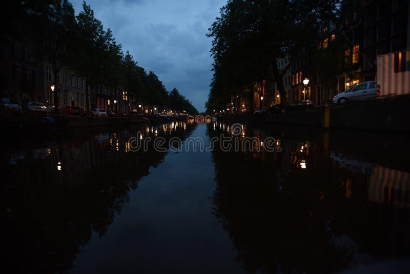 Noite em um canal de Amsterdão com as pontes leves no enc fotos de stock