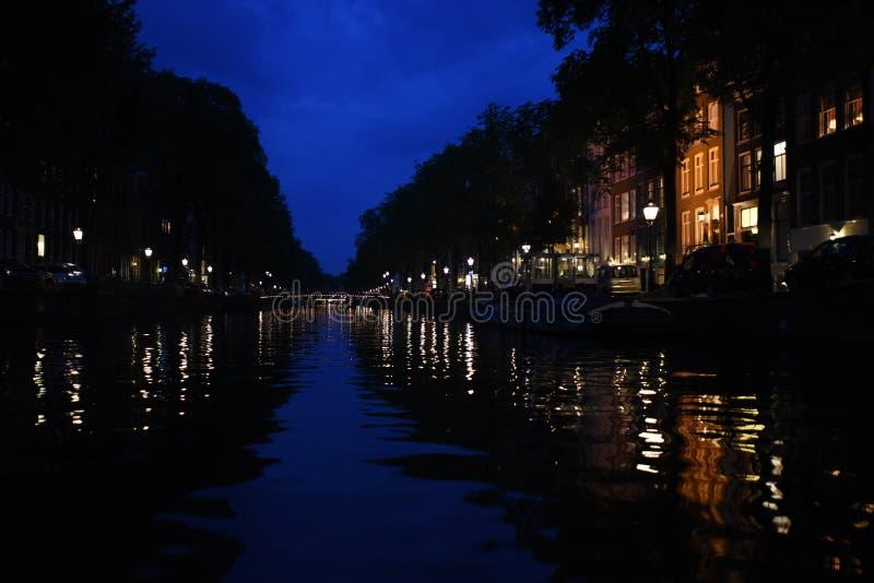 Noite em um canal de Amsterdão com as reflexões dos revérbero e das construções foto de stock