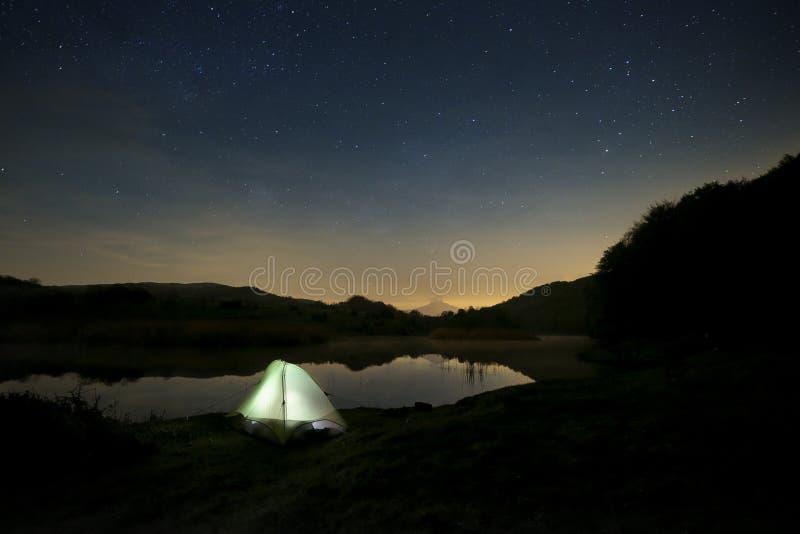 Noite estrelado no acampamento selvagem pelo lago imagem de stock