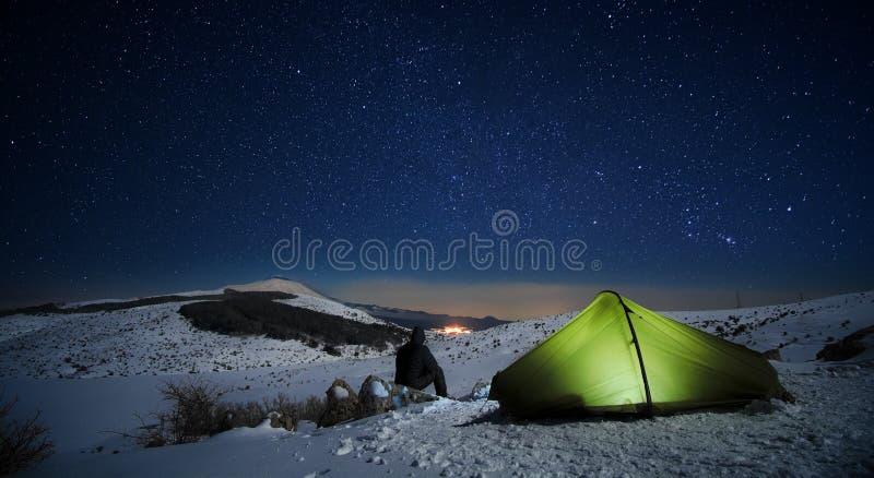 Noite estrelado no homem que olha a paisagem do inverno iluminando a barraca imagem de stock