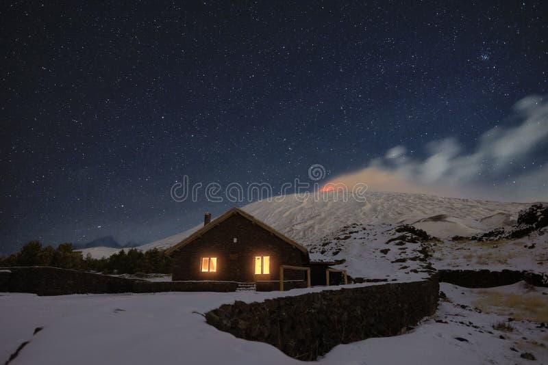 Noite estrelado no refúgio de Galvarina com as janelas que incandescem sob Etna Volcano nevado foto de stock royalty free