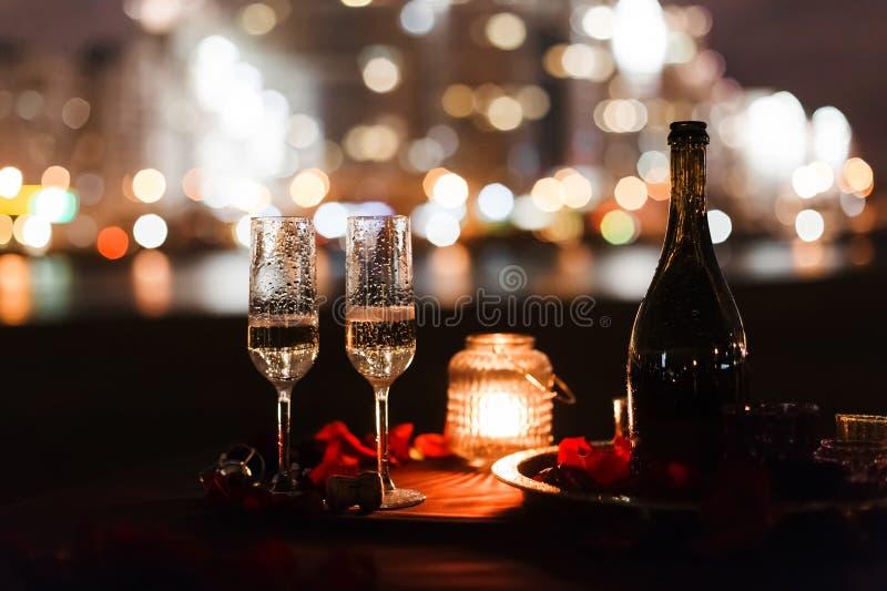A noite luxuosa romântica com o champanhe que ajusta-se com dois vidros, aumentou petails e velas imagens de stock royalty free