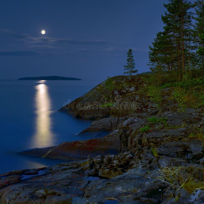 Noite Moonlit na costa rochoso do lago ladoga imagens de stock