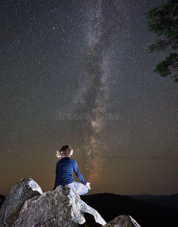 Noite nas montanhas Opinião traseira a menina magro do turista que senta-se apenas sobre o pedregulho enorme que faz a ioga fotografia de stock