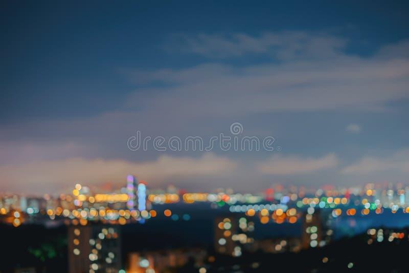 Noite urbana abstrata Cidade na noite com bokeh claro contra o céu com nuvens, foco borrado, hora crepuscular, para imagem de stock