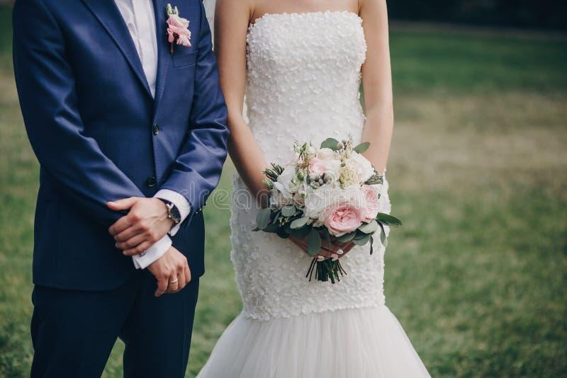 Noiva à moda com posição do ramalhete e do noivo no corredor do casamento com as pétalas cor-de-rosa na grama durante o matrimôni fotos de stock royalty free