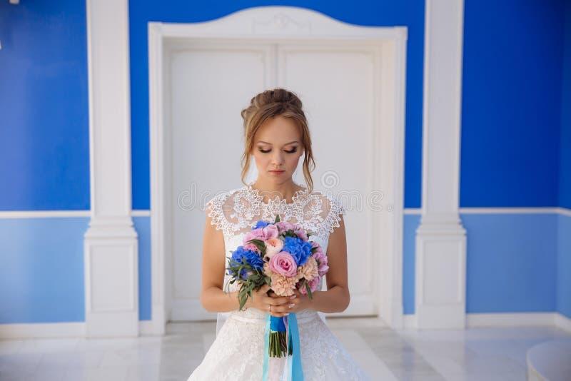 A noiva admira seu ramalhete das flores O modelo no vestido de casamento está em um grande salão azul A menina está guardando den fotos de stock royalty free