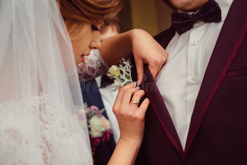 A noiva ajusta com cuidado um boutonniere no groom& x27; revestimento de s fotografia de stock