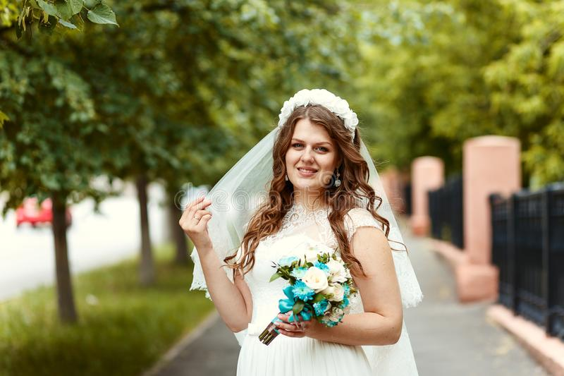 Noiva alegre bonita em um vestido branco e véu com um ramalhete em suas mãos foto de stock royalty free