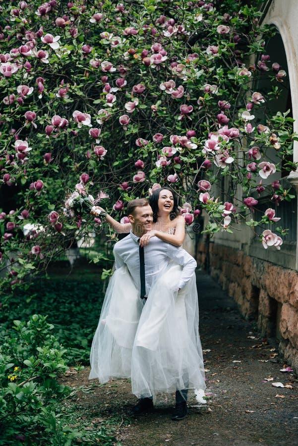 Noiva alegre e emocional nos ombros do noivo imagens de stock royalty free