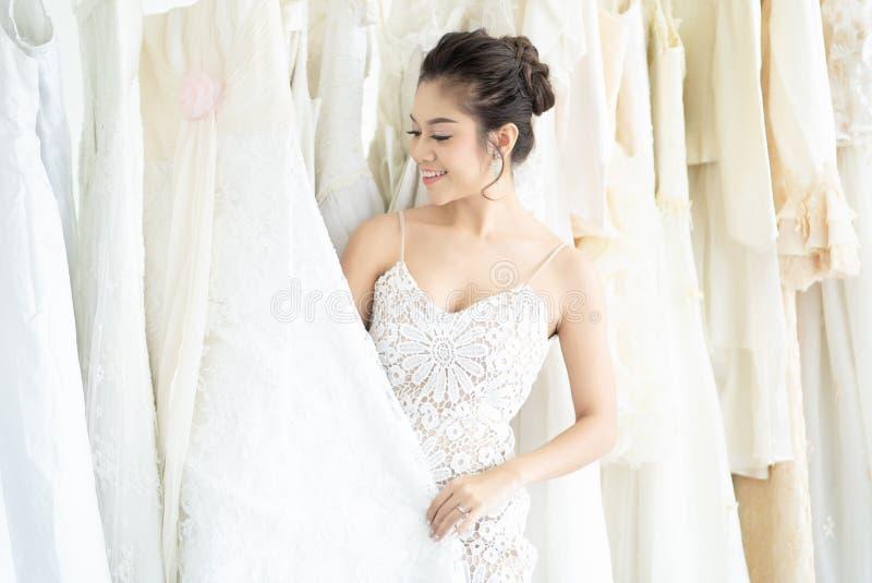 A noiva asi?tica bonita est? sorrindo ao escolher algum vestido de casamento no sal?o de beleza moderno do casamento Momentos do  fotografia de stock