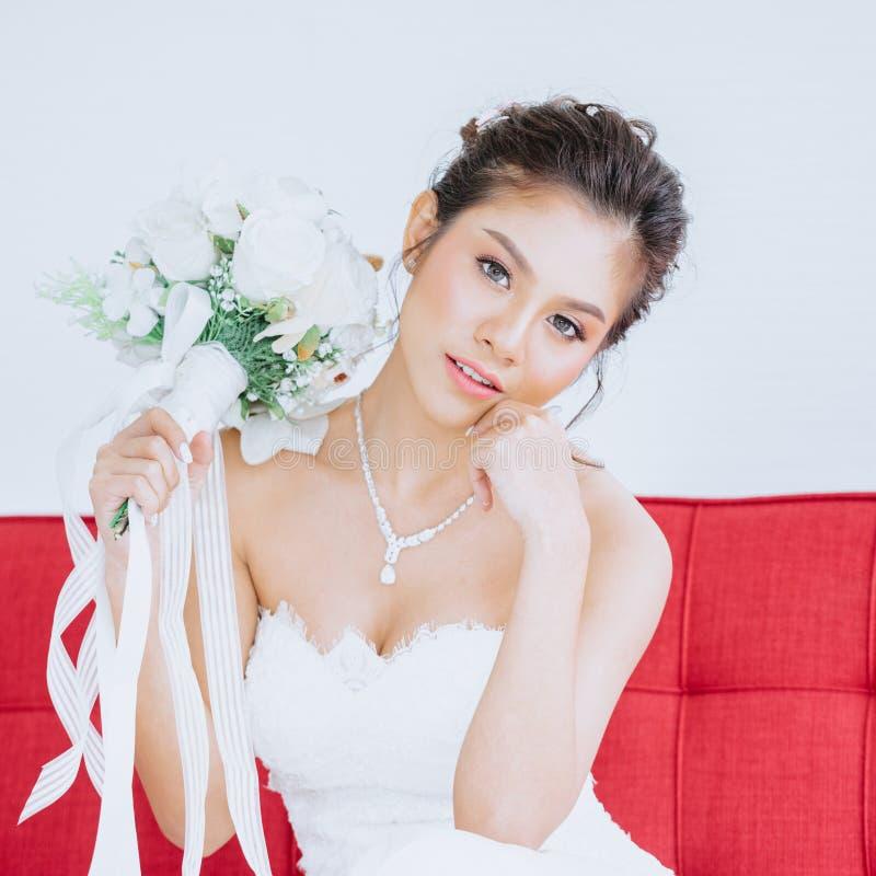 Noiva asiática bonita no vestido branco que senta-se no sofá vermelho com ramalhetes nupciais fotos de stock