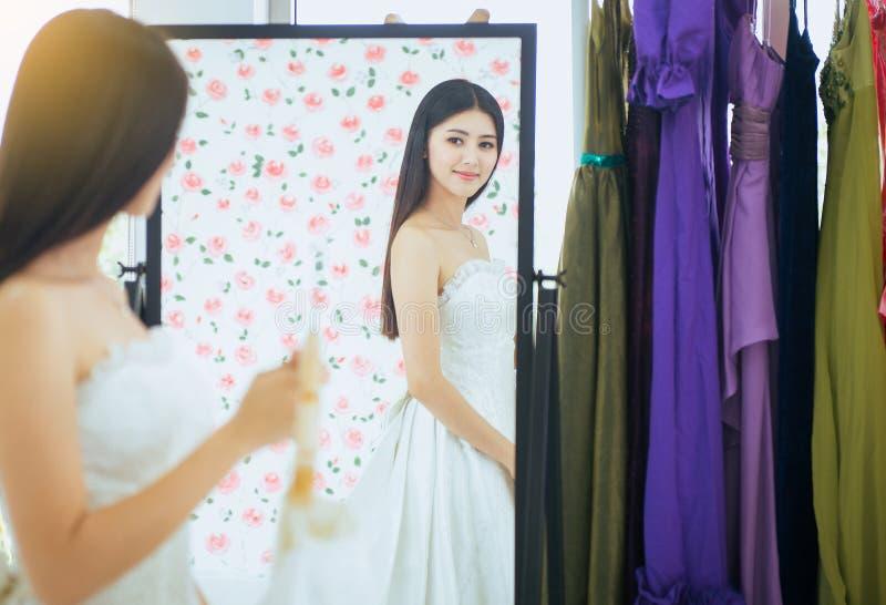 Noiva asiática nova bonita da mulher que tenta no vestido de casamento na parte dianteira do espelho, feliz e do sorriso fotos de stock royalty free