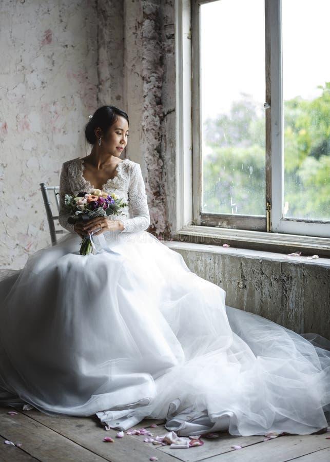 Noiva asiática que guarda a cerimônia do acoplamento do casamento do ramalhete da flor fotografia de stock