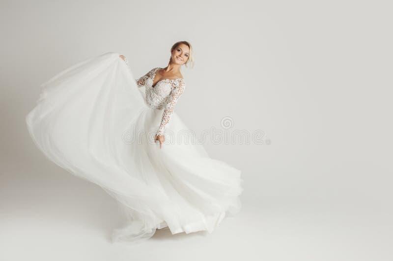 Noiva atrativa bonita no vestido de casamento com o saião longo, fundo branco, dança e sorriso foto de stock royalty free