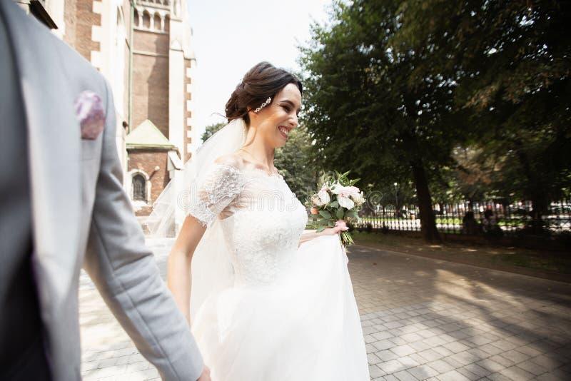 A noiva bonita anda com seu noivo perto da igreja cristã velha imagem de stock royalty free