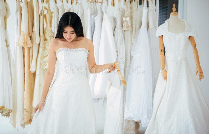 Noiva bonita asiática das jovens mulheres que tenta no vestido de casamento, feliz e no sorriso imagens de stock royalty free