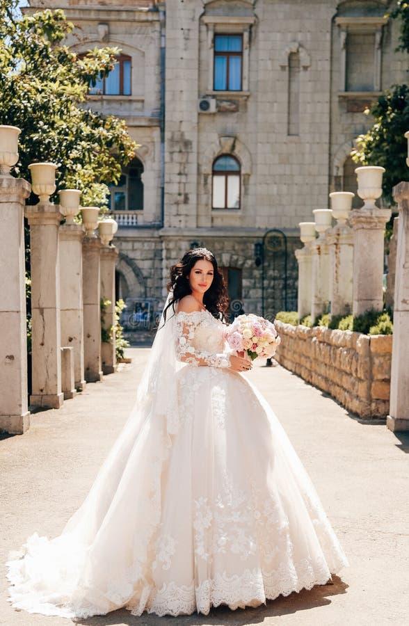 Noiva bonita com cabelo escuro no vestido de casamento luxuoso no ele imagens de stock