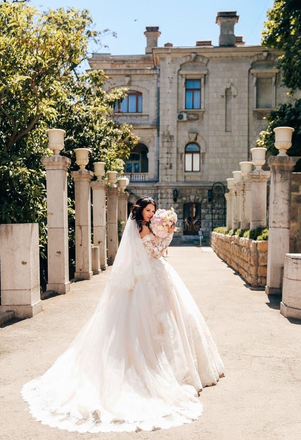 Noiva bonita com cabelo escuro no vestido de casamento luxuoso no ele fotos de stock