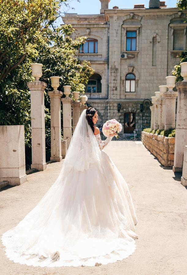 Noiva bonita com cabelo escuro no vestido de casamento luxuoso no ele fotografia de stock