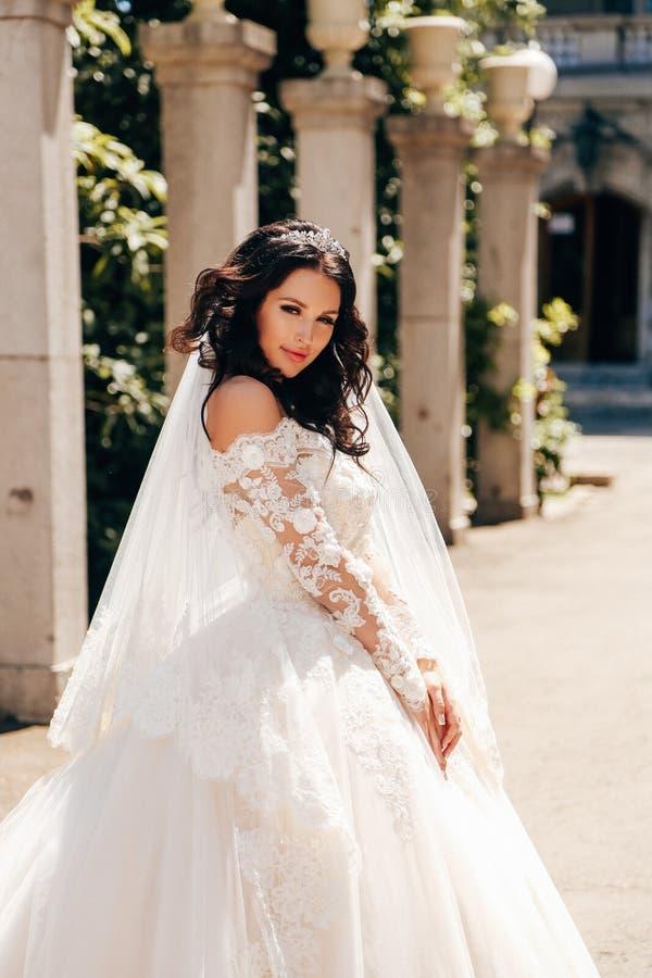 Noiva bonita com cabelo escuro no vestido de casamento luxuoso no ele foto de stock