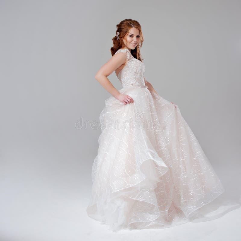 Noiva bonita da jovem mulher no vestido de casamento pródigo Fundo claro imagens de stock