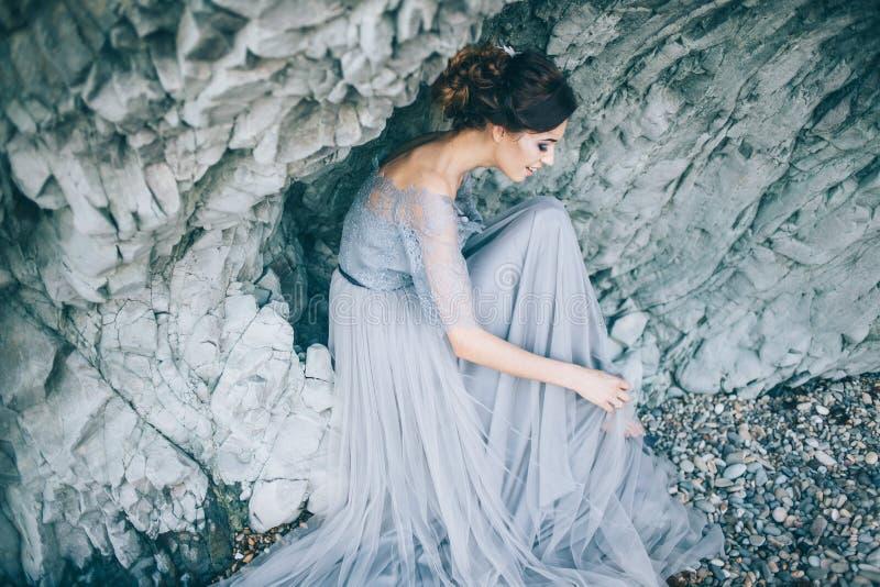 A noiva bonita da menina em um vestido cinzento que senta-se pelo mar perto da rocha sorri, ri, endireita seu vestido do laço imagens de stock royalty free