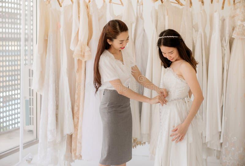 A noiva bonita da mulher que tenta no vestido de casamento branco, mulheres asiáticas costura a fatura do ajuste em seu cliente d fotografia de stock royalty free