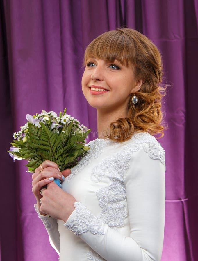 Noiva bonita de sorriso com o ramalhete das flores imagem de stock royalty free