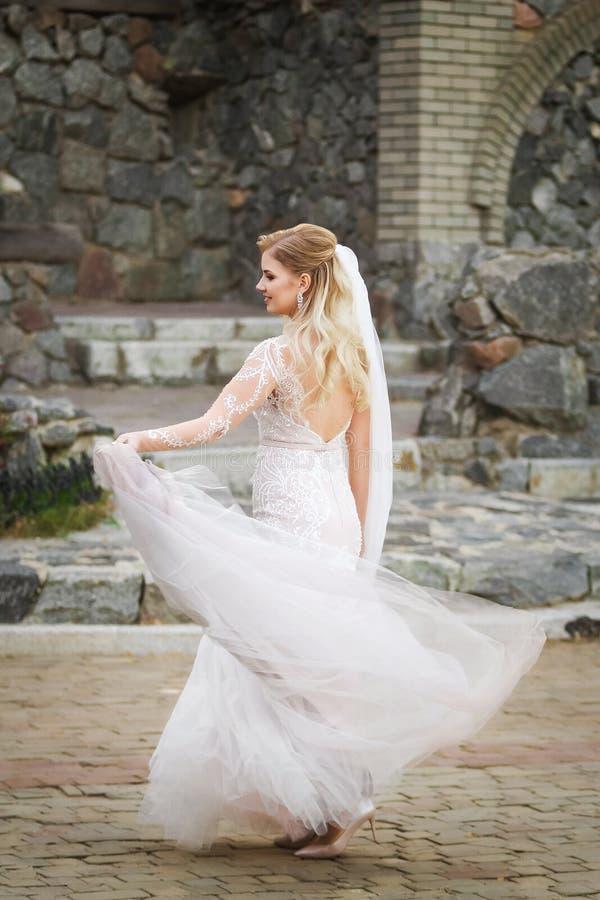Noiva bonita de sorriso que mantém para trás a saia longa do vestido de casamento imagens de stock royalty free