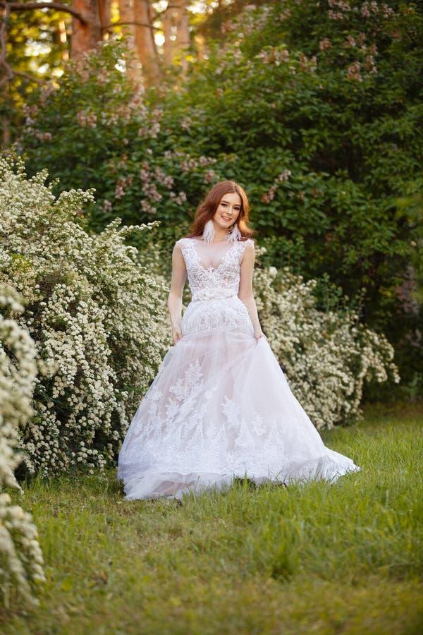 Noiva bonita do ruivo no vestido de casamento fantástico no jardim de florescência foto de stock royalty free