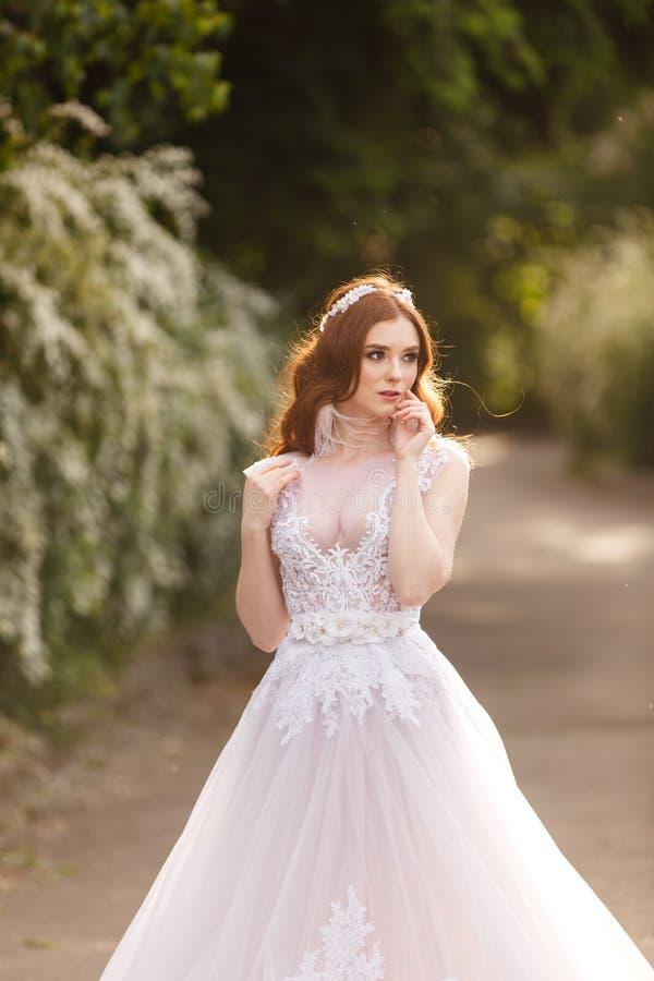 Noiva bonita do ruivo no vestido de casamento fantástico no jardim de florescência fotografia de stock