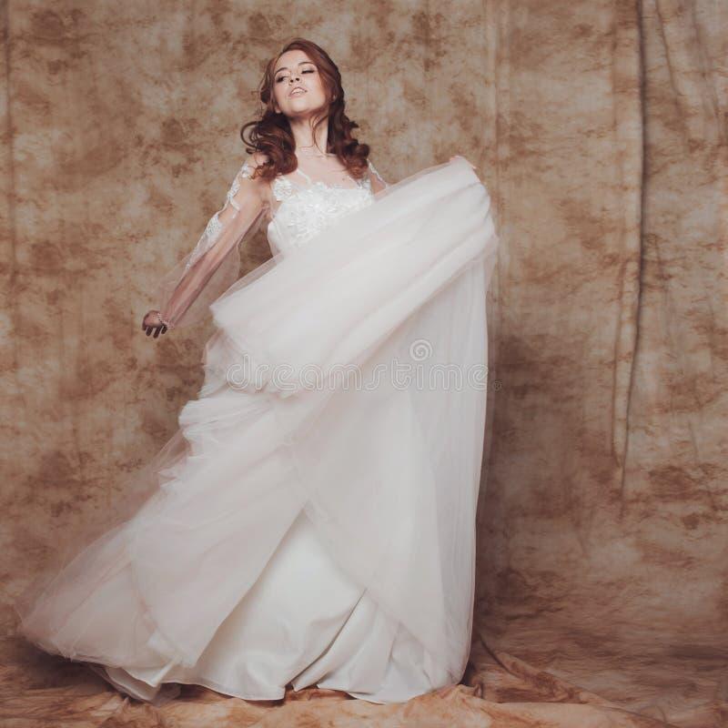 Noiva bonita e romântica no vestido de casamento com a saia leve e macia Mulher redheaded nova no vestido de casamento foto de stock