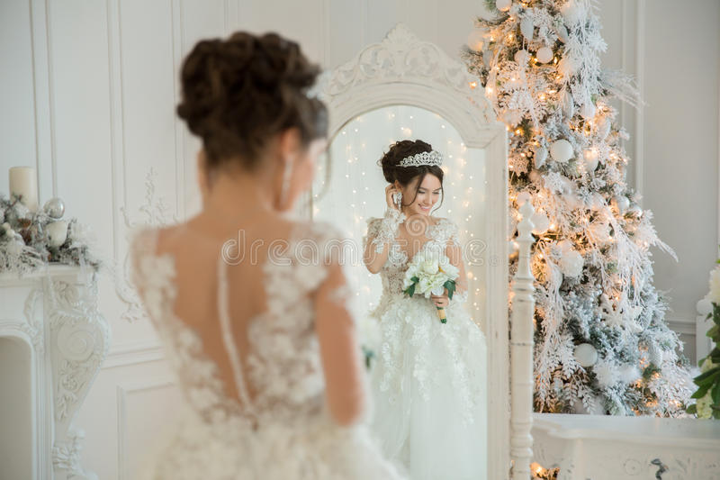 Noiva bonita em um vestido de casamento em um espelho no Natal Gir fotografia de stock royalty free