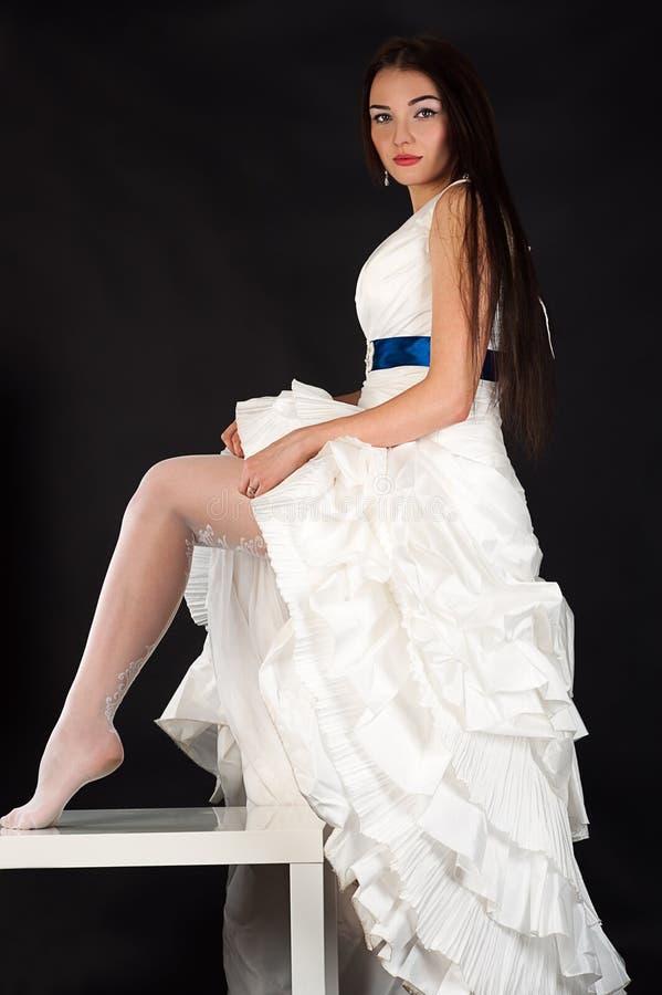 A noiva bonita em um vestido de casamento endireita meias fotografia de stock
