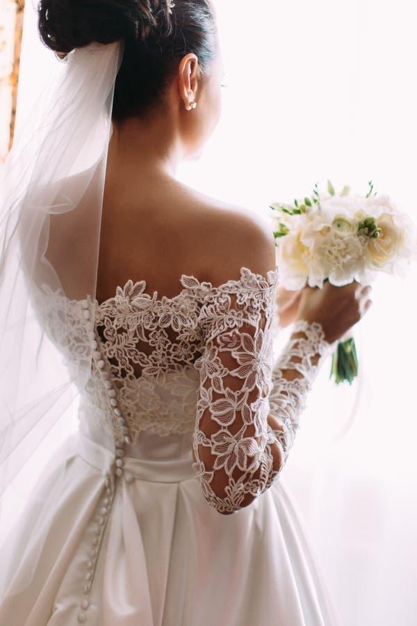 A noiva bonita está guardando o ramalhete do casamento das rosas brancas A opinião traseira do close-up fotografia de stock