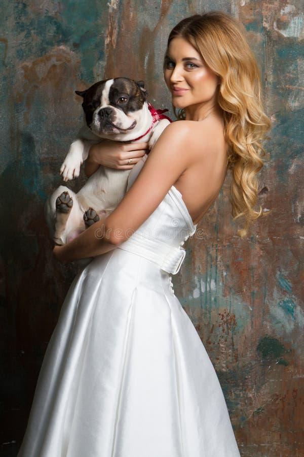 A noiva bonita está guardando um cão imagens de stock royalty free