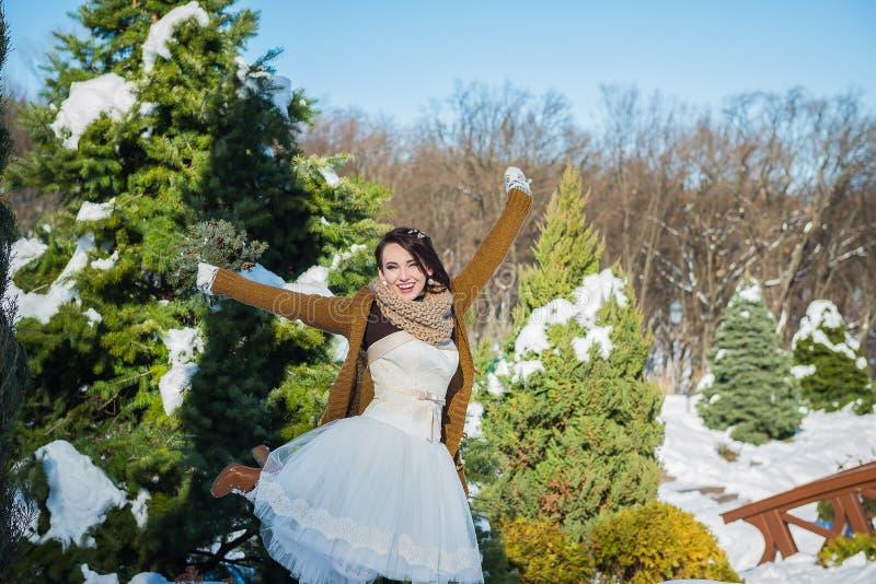 Noiva bonita feliz em um dia de inverno nevado tempo ensolarado stylish com o ramalhete do casamento feito do pinheiro feito à mã fotografia de stock royalty free